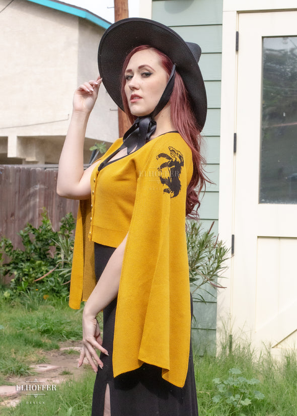Kelsey is modeling the yellow cropped cardigan with a black badger on the sleeve. The sleeve is open on the underside.