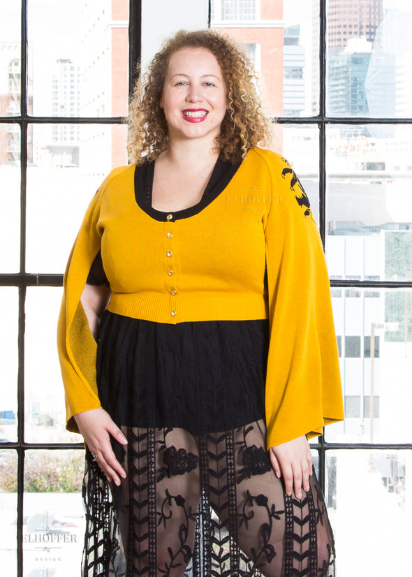 "Anastasia is modeling a Production XL yellow cropped cardigan with cape sleeves. She has a 45"" Bust, 39"" Waist, and 49"" Hip and is 5'9""."