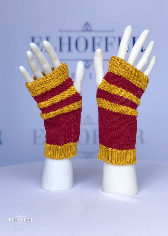 A pair of fingerless gloves with thumbholes. They have alternating golden yellow and red with golden yellow ribbing at the fingers and wrist.