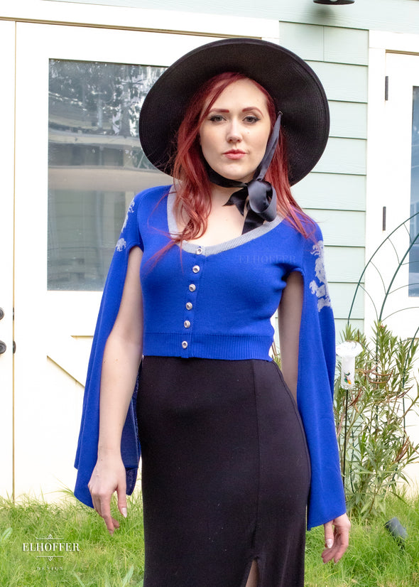 Kelsey pairs the cropped blue cape sleeve cardigan with a witchy hat and black maxi dress.