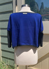 The back of the cobalt blue oversized cropped sweater with a gray neckline and sleeves.