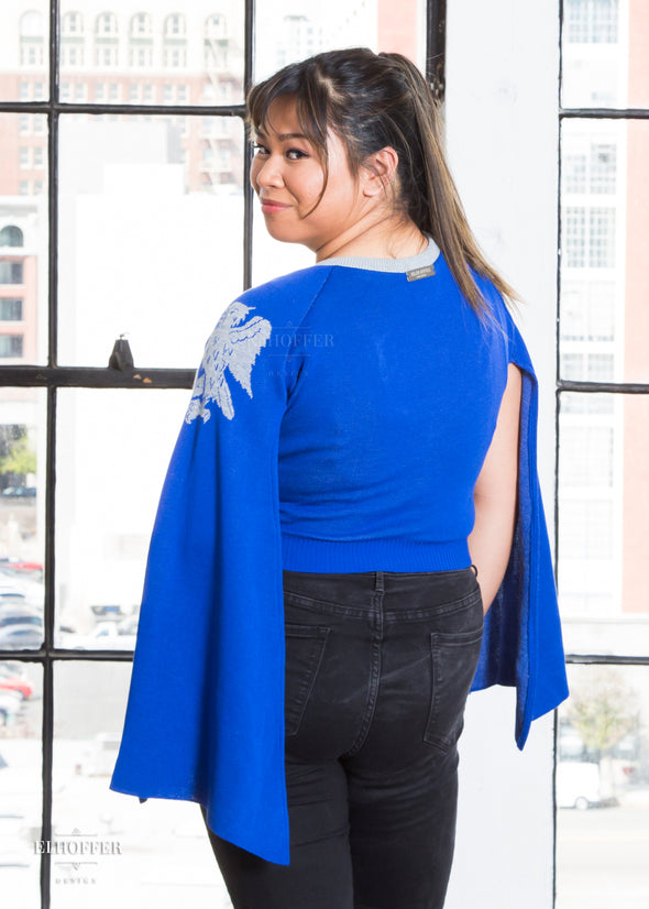 Nik models the back of the cropped blue sweater with cape sleeves.
