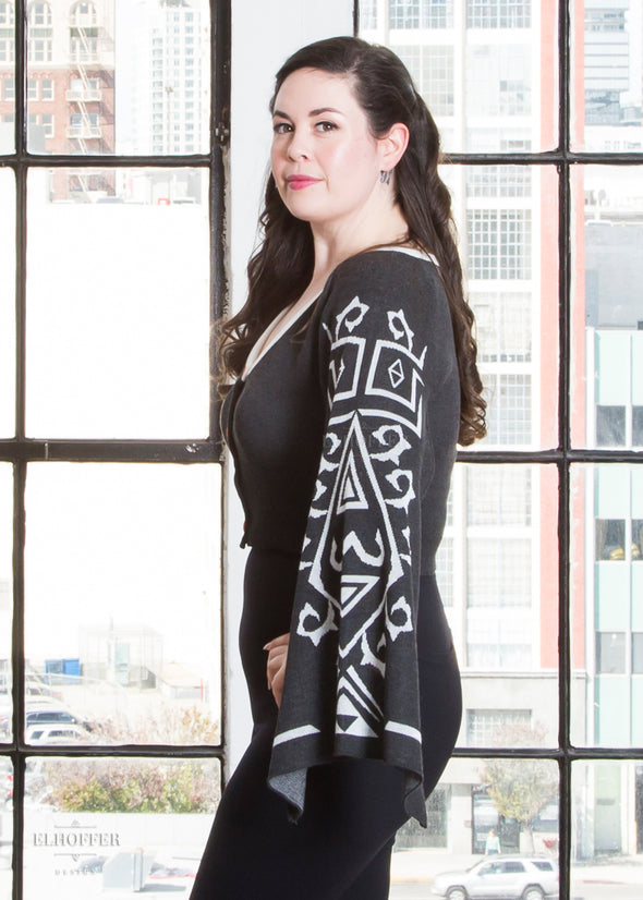 Devan shows the white design on the gray cape sleeve of the cardigan