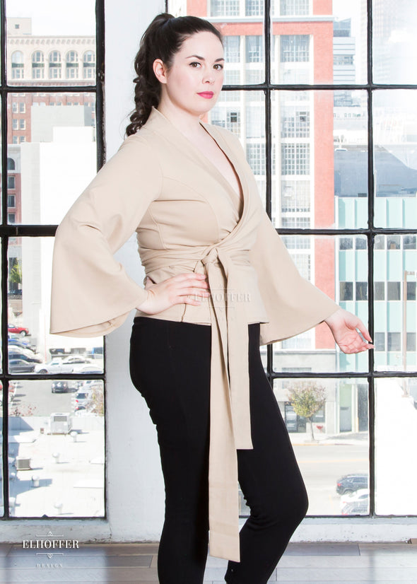 Devan models the sand colored wrap top with v neck, bell sleeves, and attached fabric belt.