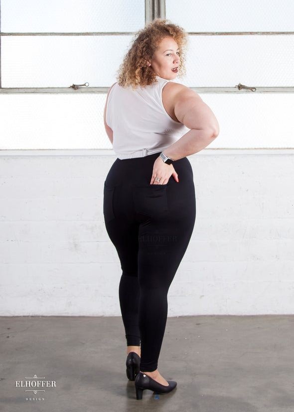 Anastasia shows the full size pockets of the black high waisted leggings.