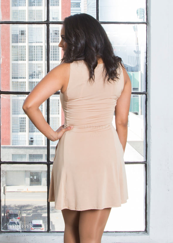 Malinda models the back of the caramel slip dress. The back hem falls to her upper mid thigh. She is 5'3.