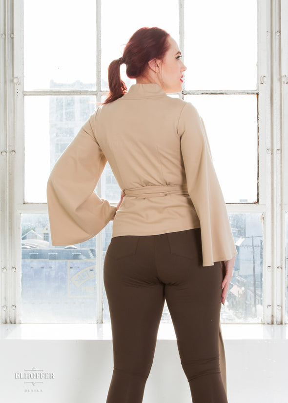 Kelsey models the back of the sand wrap top.