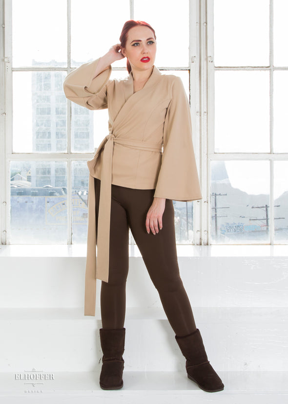 Kelsey models the sand colored wrap top with v neck, bell sleeves, and attached fabric belt.