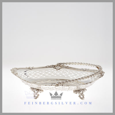Feinberg Silver | The oval English silver plated basket has an applied scroll and shell border with pierced sides and a central shield.