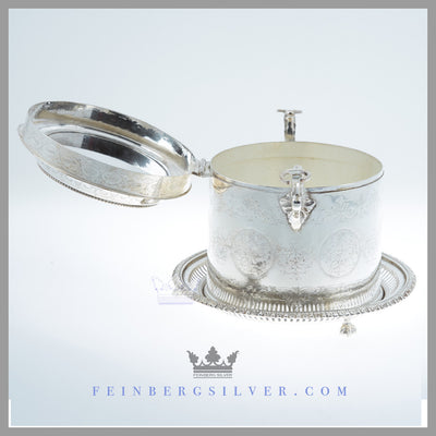 The unusual, round antique English silver plated biscuit box has an indentation on the lid to hold a flat bottom decanter. Feinberg Silver