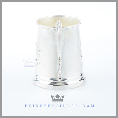 The Antique English Silver Child's Mug's tapered vertical body has a stepped rim foot and has a cast double scroll handle.