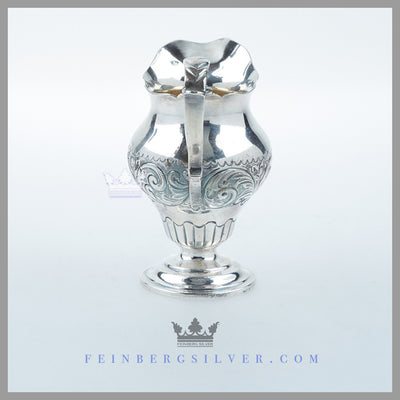 The Antique English Silver Geo III Style Cream Pitcher is baluster form and hand chased. Feinberg Silver
