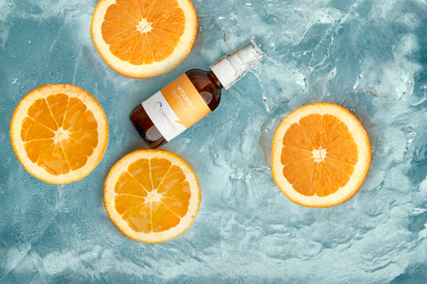 Vitamin C Serum surrounded by oranges in water