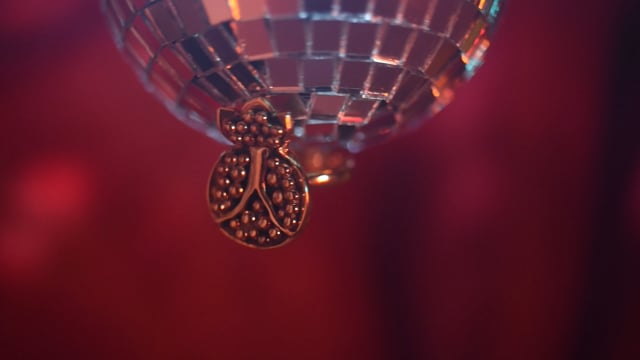Video of gold plated pomegranate/anar ring on a disco ball circling for 10 seconds. Holographic green, yellow and red colors surround the ring.