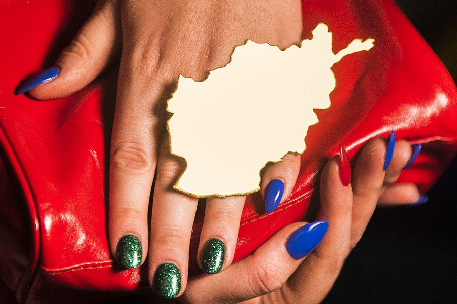 The OG Wataan Three Finger Afghan Map Knuckle Ring - Blingistan, person with blue and green sparkle nails wearing oversized ring.