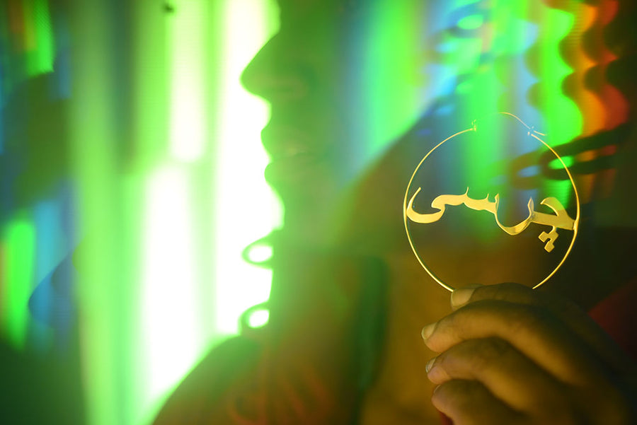 woman holding hoop earring with 'charsi' written in the middle, green and holographic colors in the back.