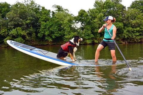 maria on the paddleboard in float coat with her dog
