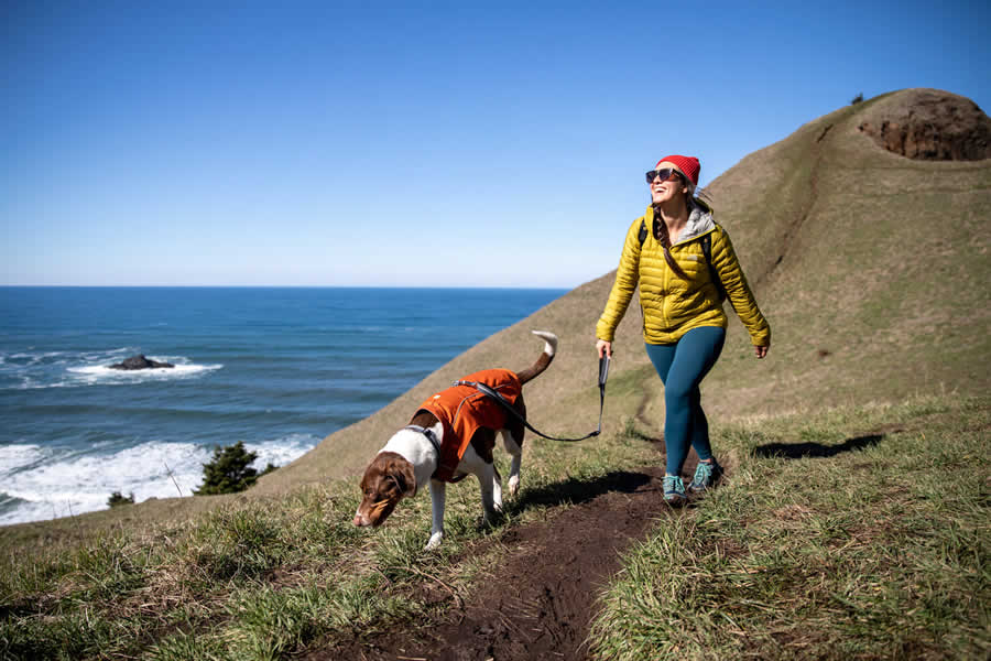 Woman hikes along Oregon coast in the sun with dog on leash clipped to overcoat fuse.