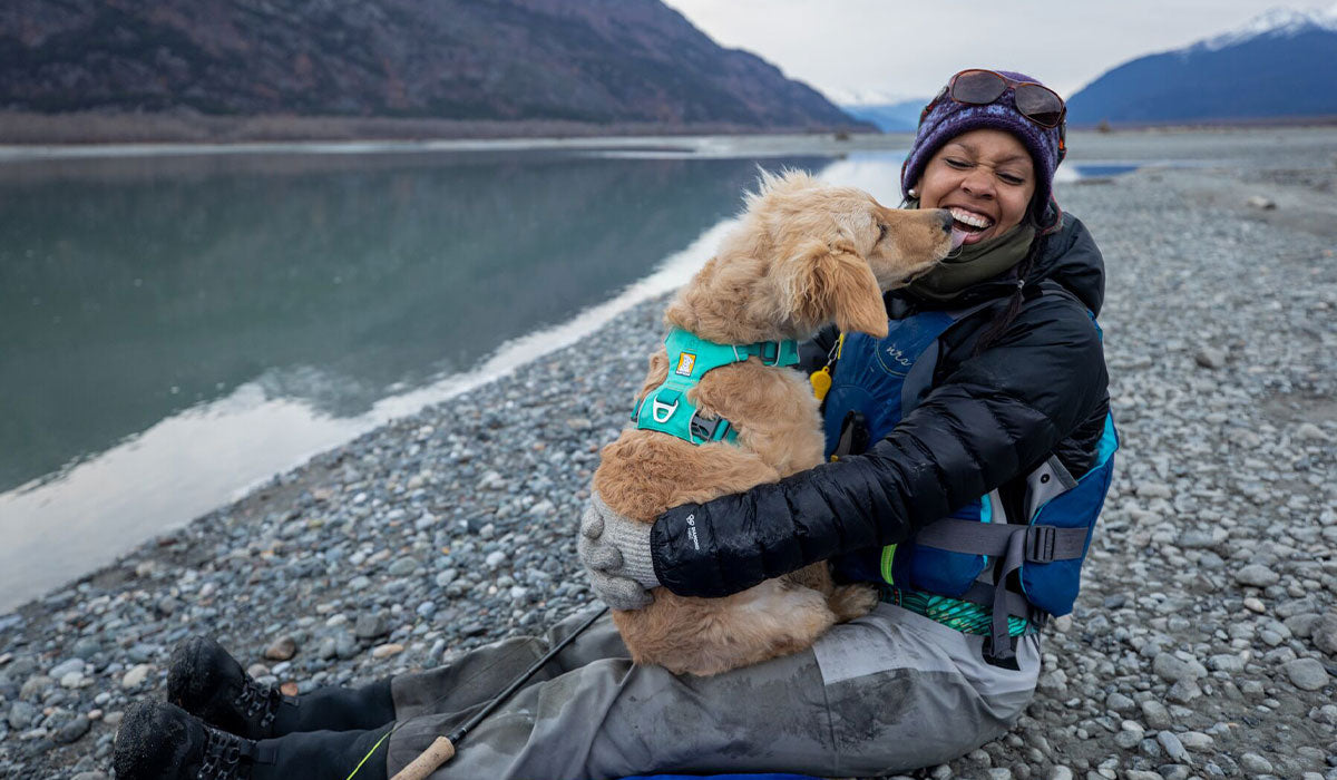 Ambassador Chrissy sits on a river beach getting kisses from her golden puppy who is wearing an aurora teal front range harness.