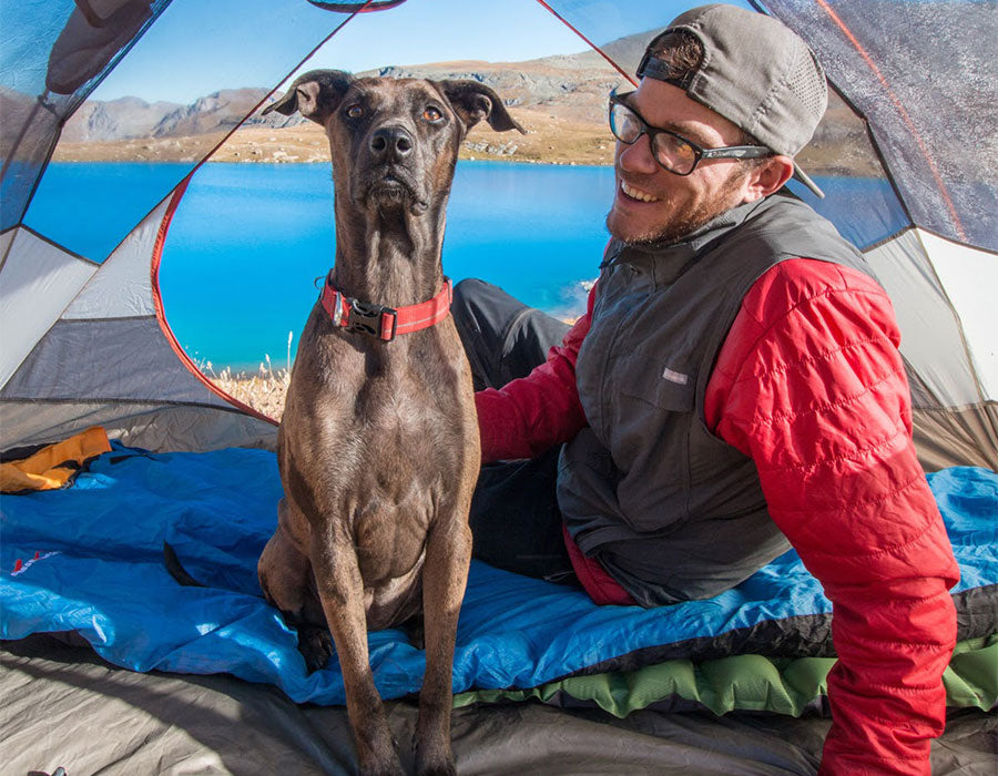 Trevor and Kahlua in a tent by a lake.