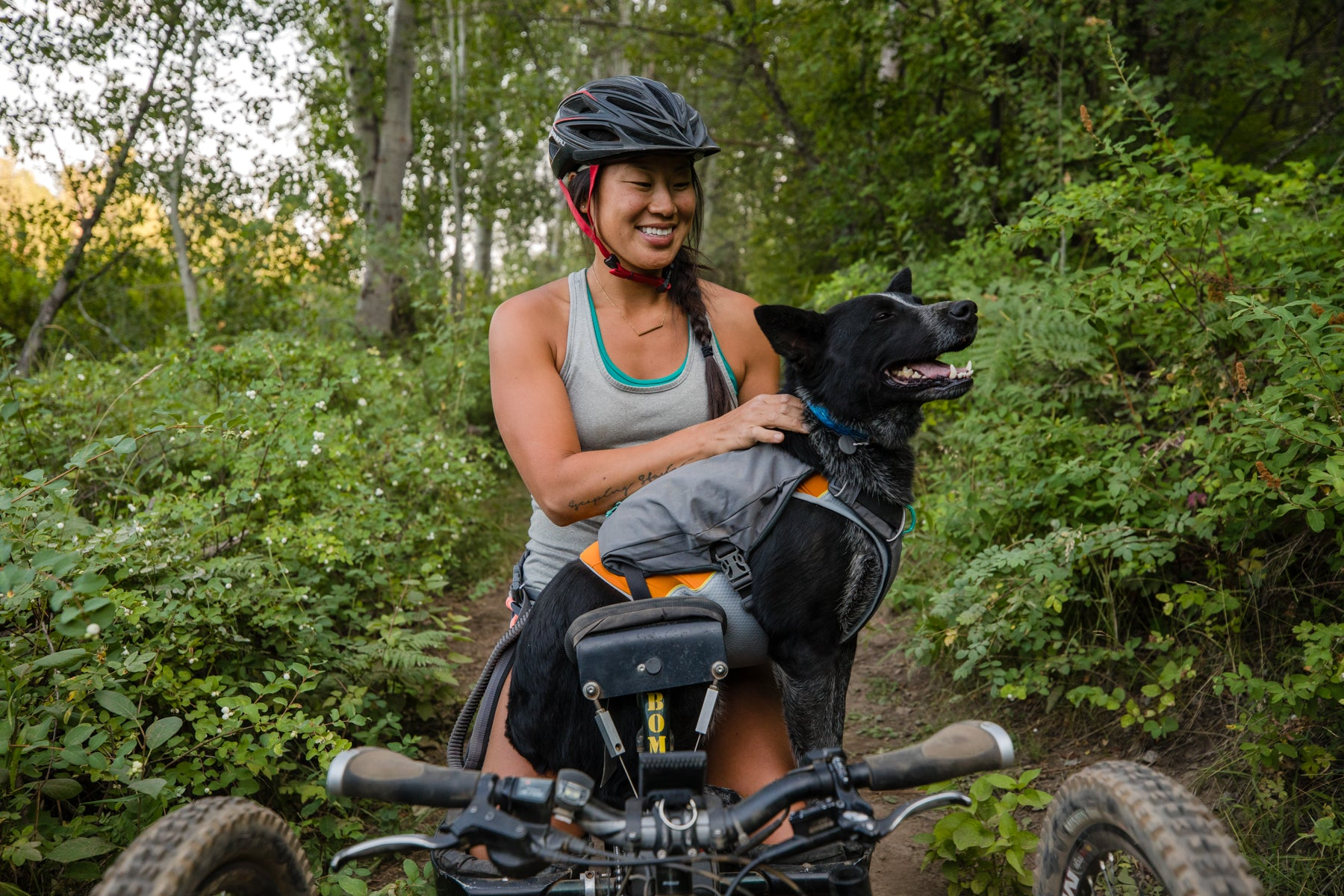 Bernie in Switchbak harness with Jet stream cooling vest underneath sits on Anna's lap on the off road handcycle.