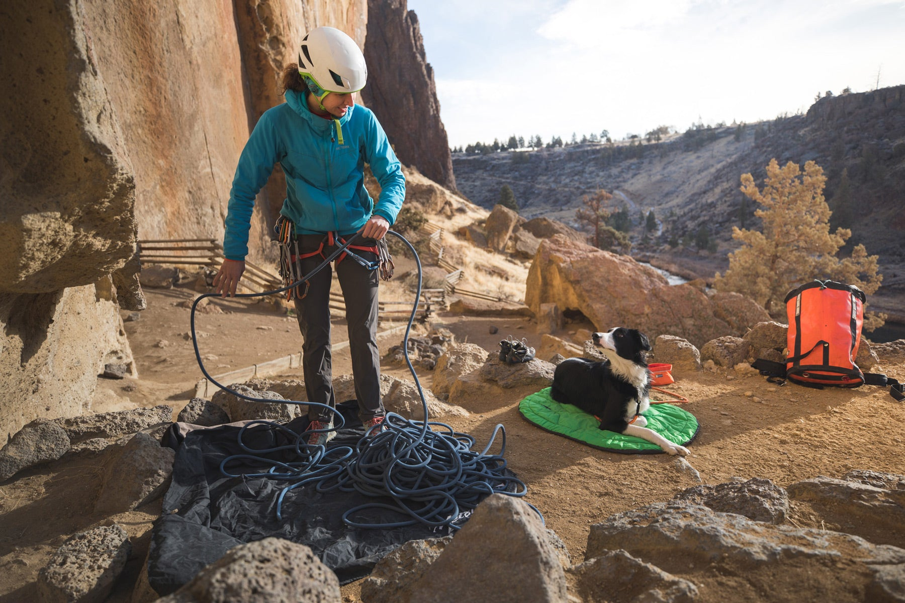 Woman flakes out climbing rope while dog lays on highland dog sleeping bag.
