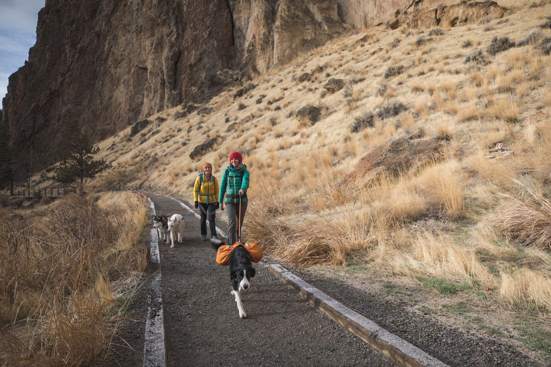 Two climbers with their dogs in approach packs walk out on the trail at Smith Rock.