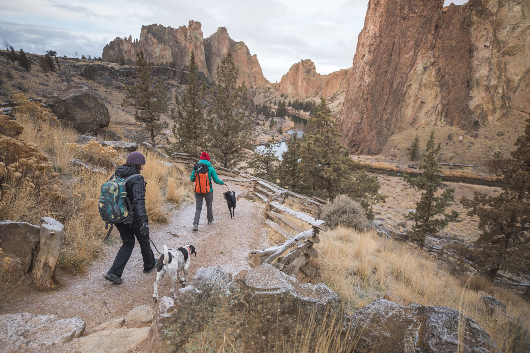 Two climbers with dogs on knot-a-leashes descend on the trail at Smith.