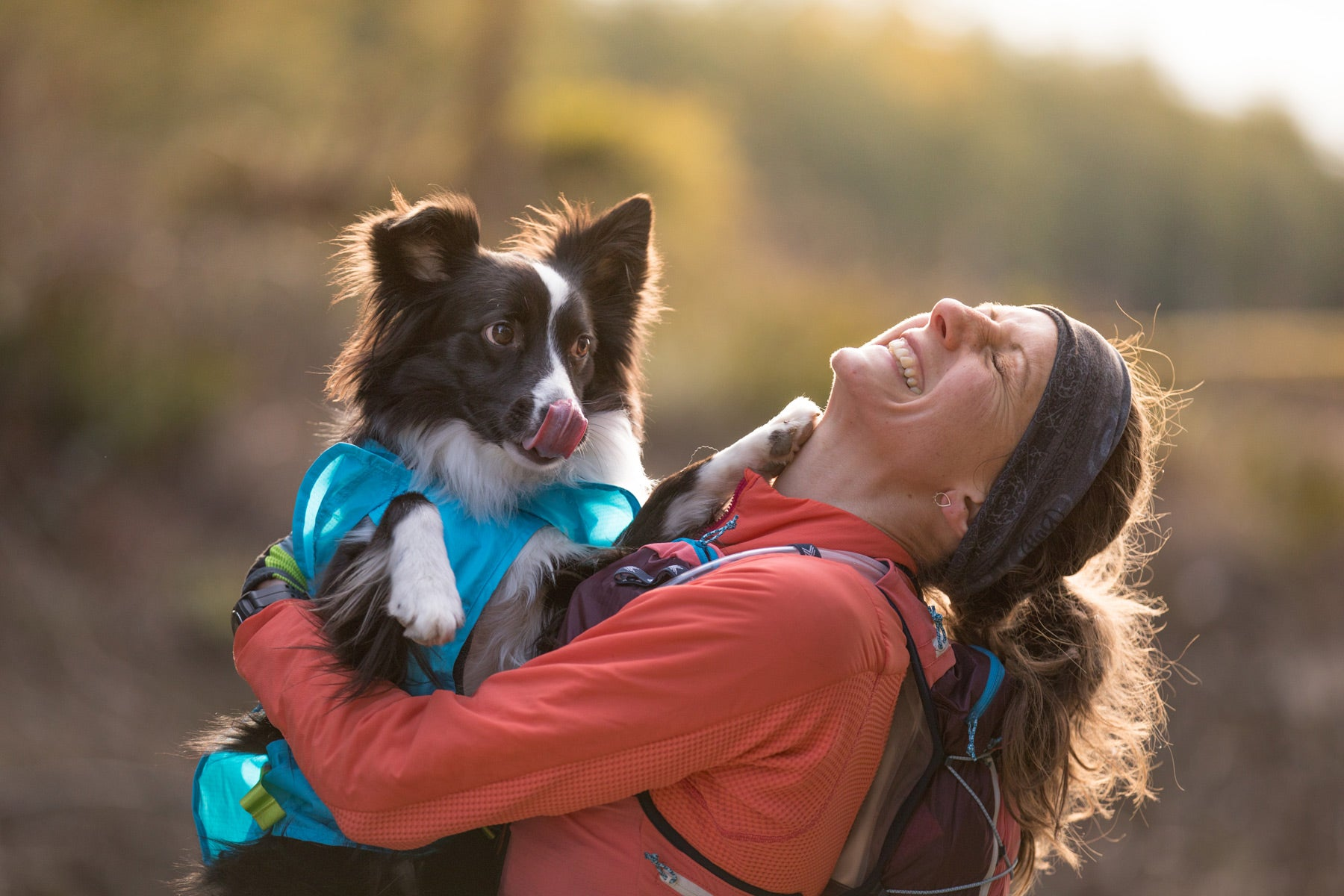 Krissy smiles and laughs while holding PD in her arms while on a trail run.