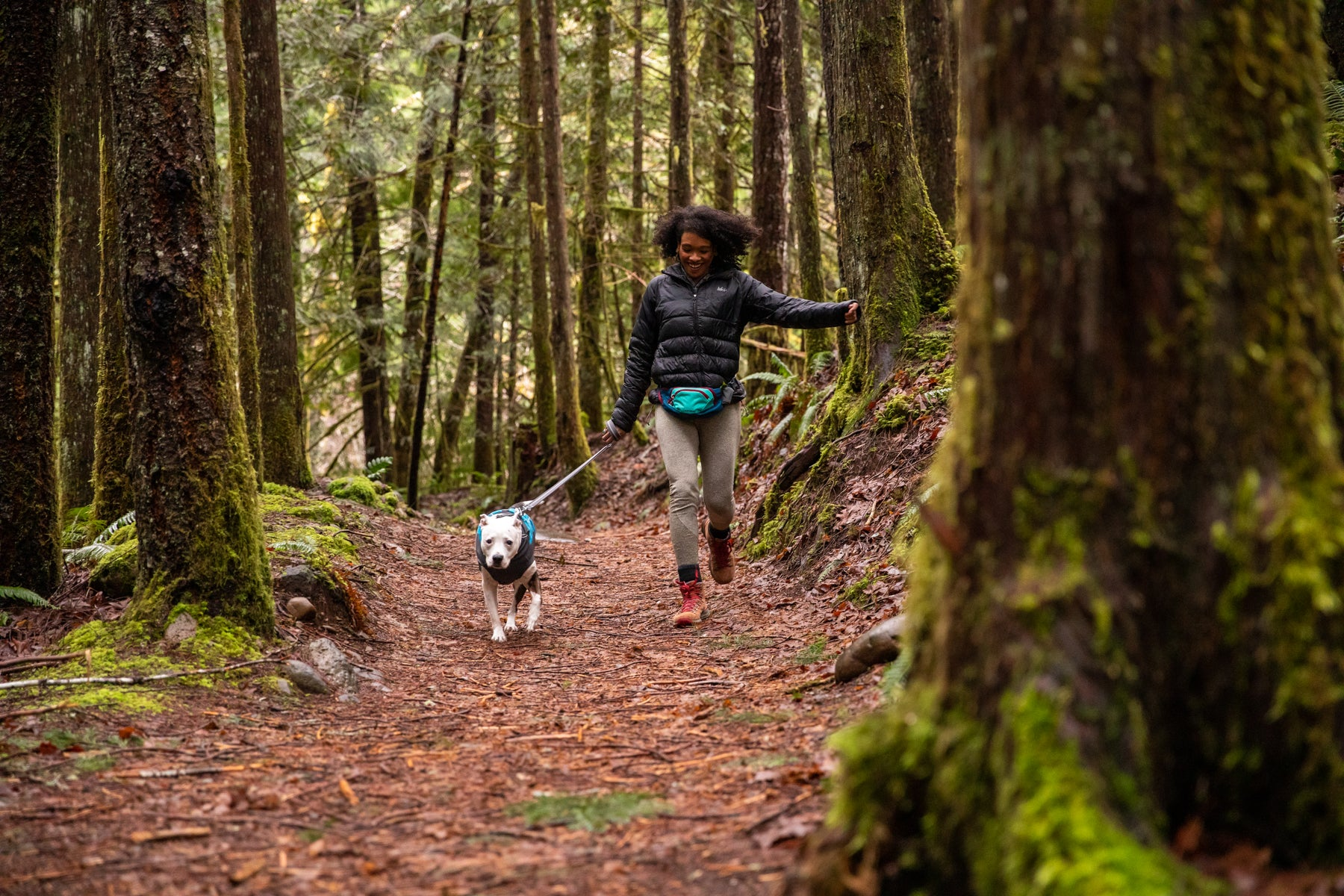 Woman and dog skip through green forested trail.