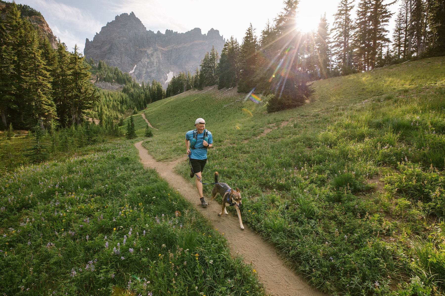 Dog and human run along trail with wildflowers.