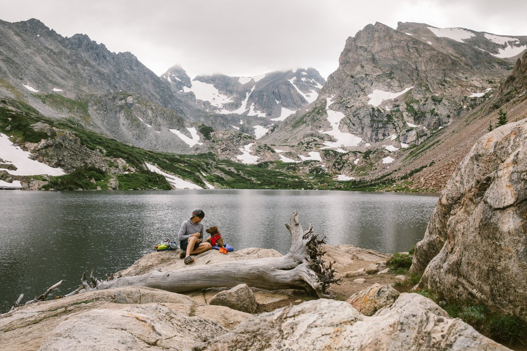 Nathan and Turkey sit on a rock by an alpine lake for a snack break.