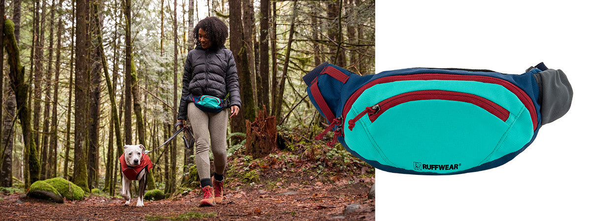 Alexis wears home trail hip pack and walks dog Cookie, wearing a overcoat, through Forest Park.