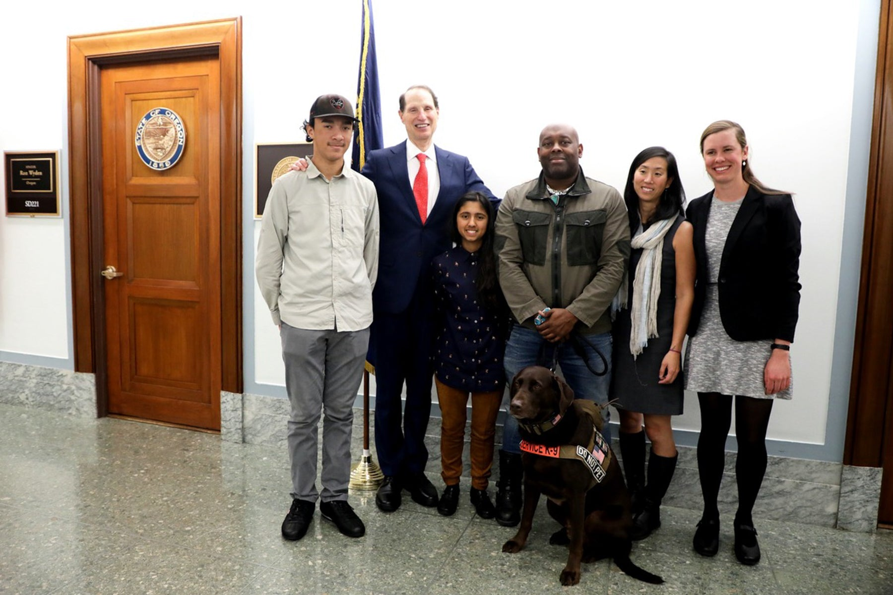Chad and Axe and group of individuals take a photo with congressperson at Oregon state capital.