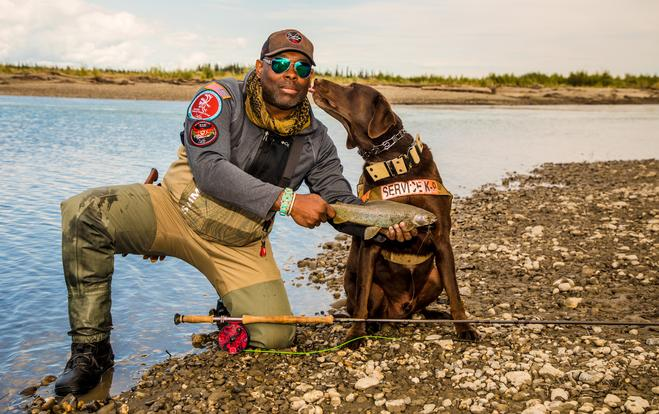 Chad holds up a fish kneeling by the river in fly fishing gear while dog Axe gives him a kiss on the cheek.