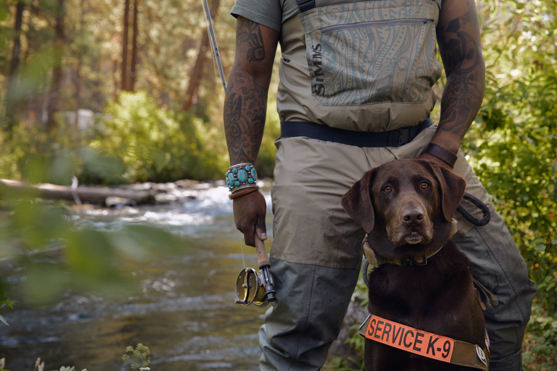 Chad in fly fishing gear and dog axe in service dog vest pose by the river close up.