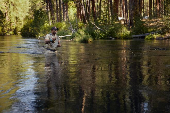 Chad stands fly fishing in the middle of the river.