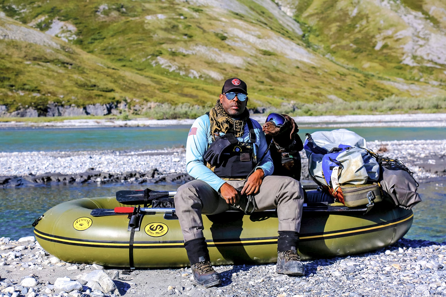 Chad and Axe in water gear and sunglasses sit on a raft next to the river.