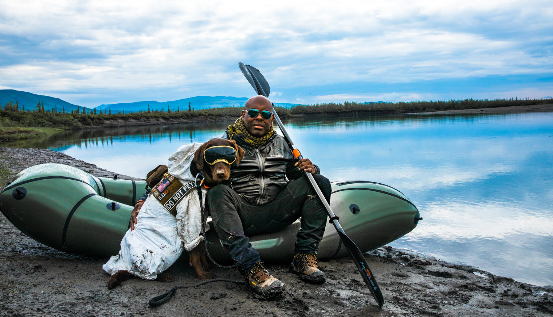 Chad and Axe sit by a packraft next to a lake with very blue skies in the background.