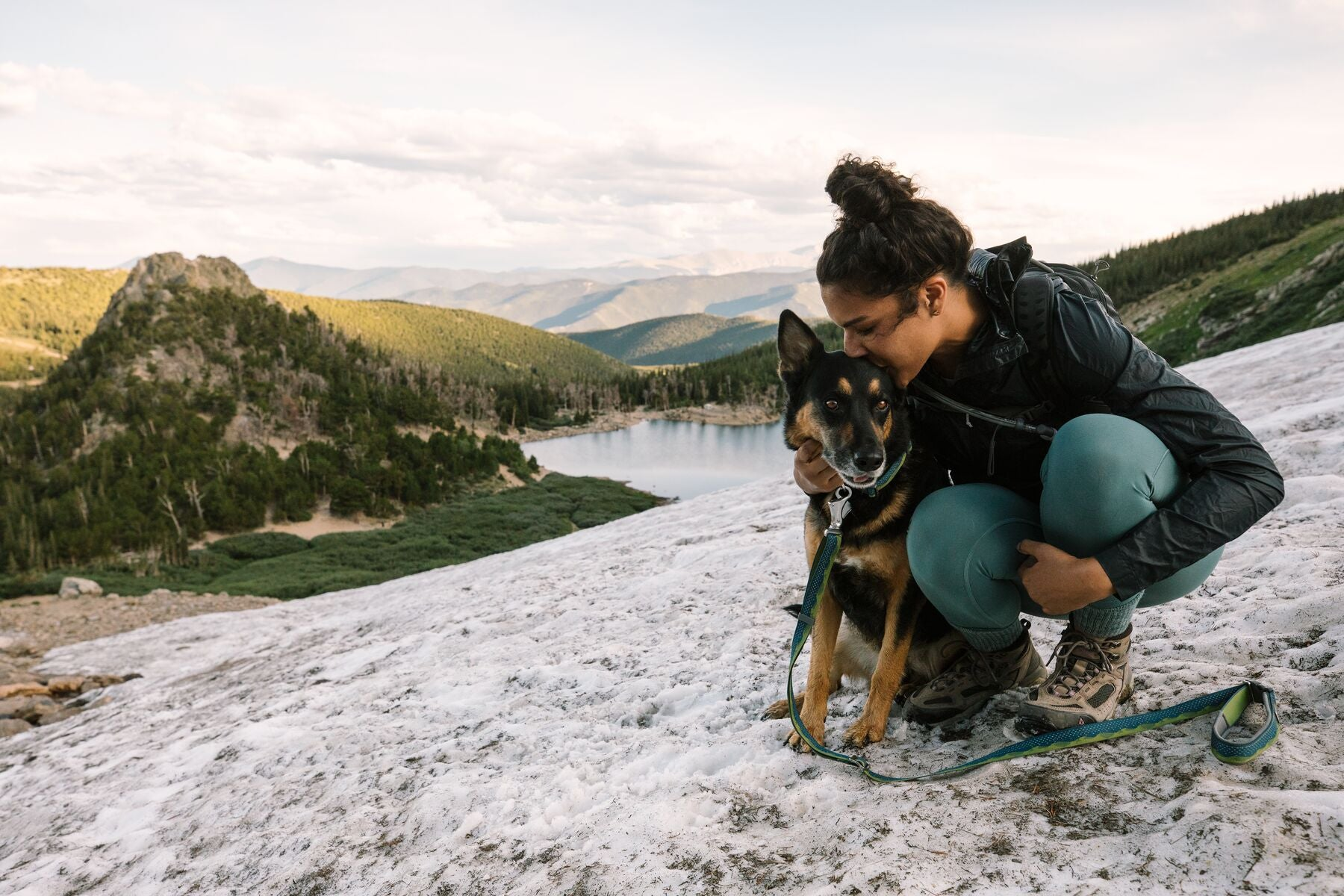 Woman gives dog wearing flat out collar and leash a kiss while sitting on the snow above an alpine lake.