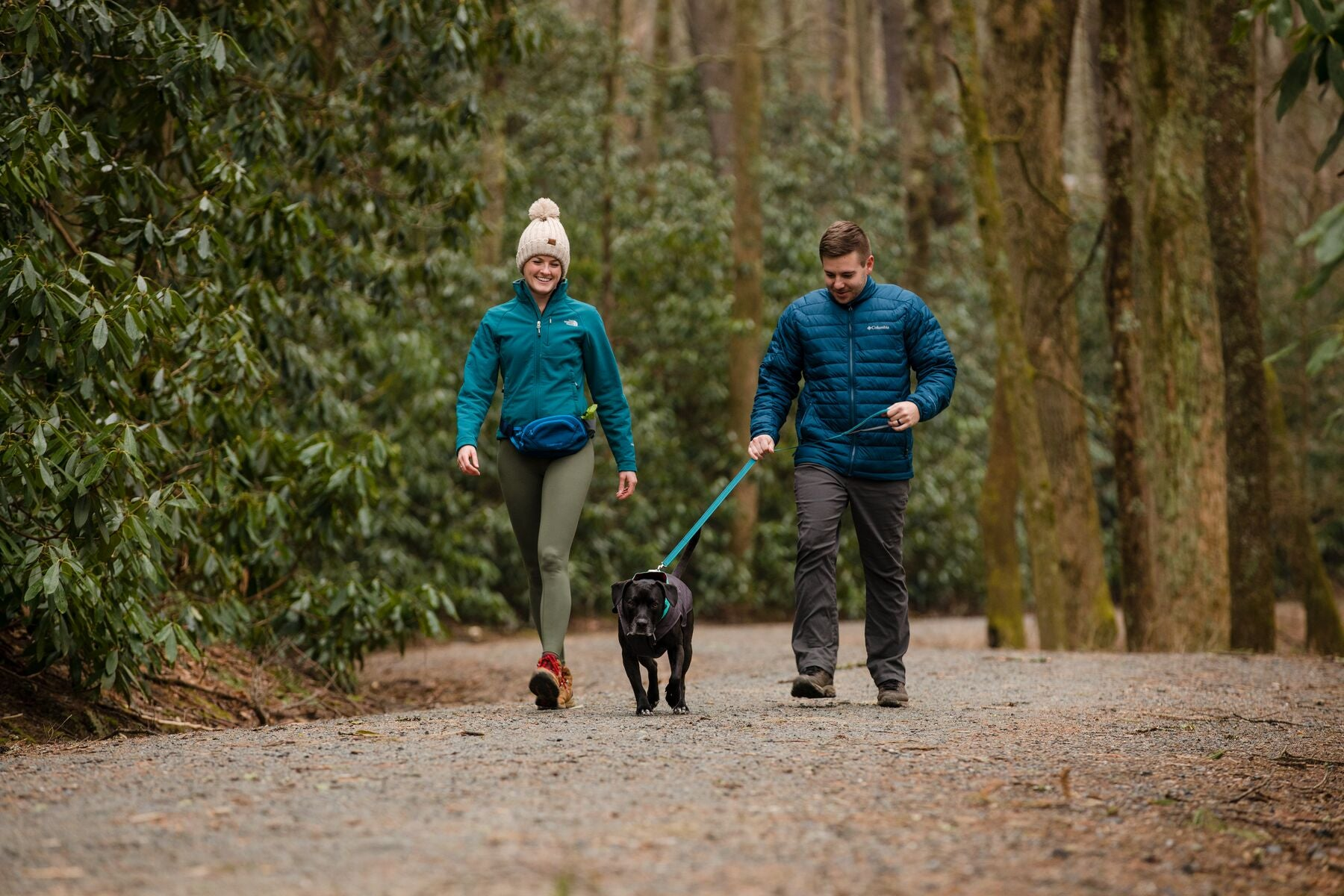 Woman wearing home trail hip pack walks with man and dog in a park.