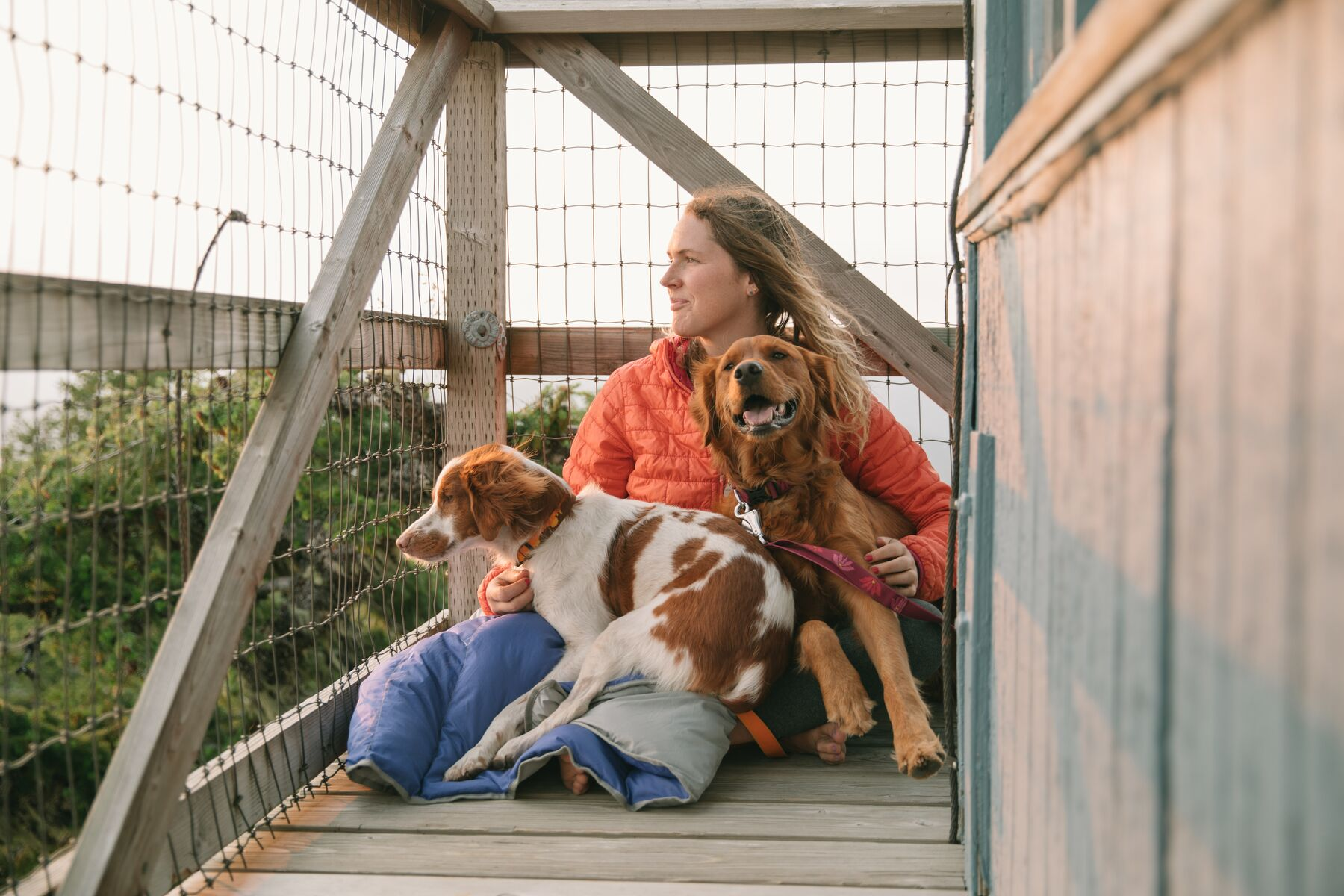Elise enjoys the view from a fire lookout with dogs Ubu and Bailey wrapped in a clear lake blanket at her side.