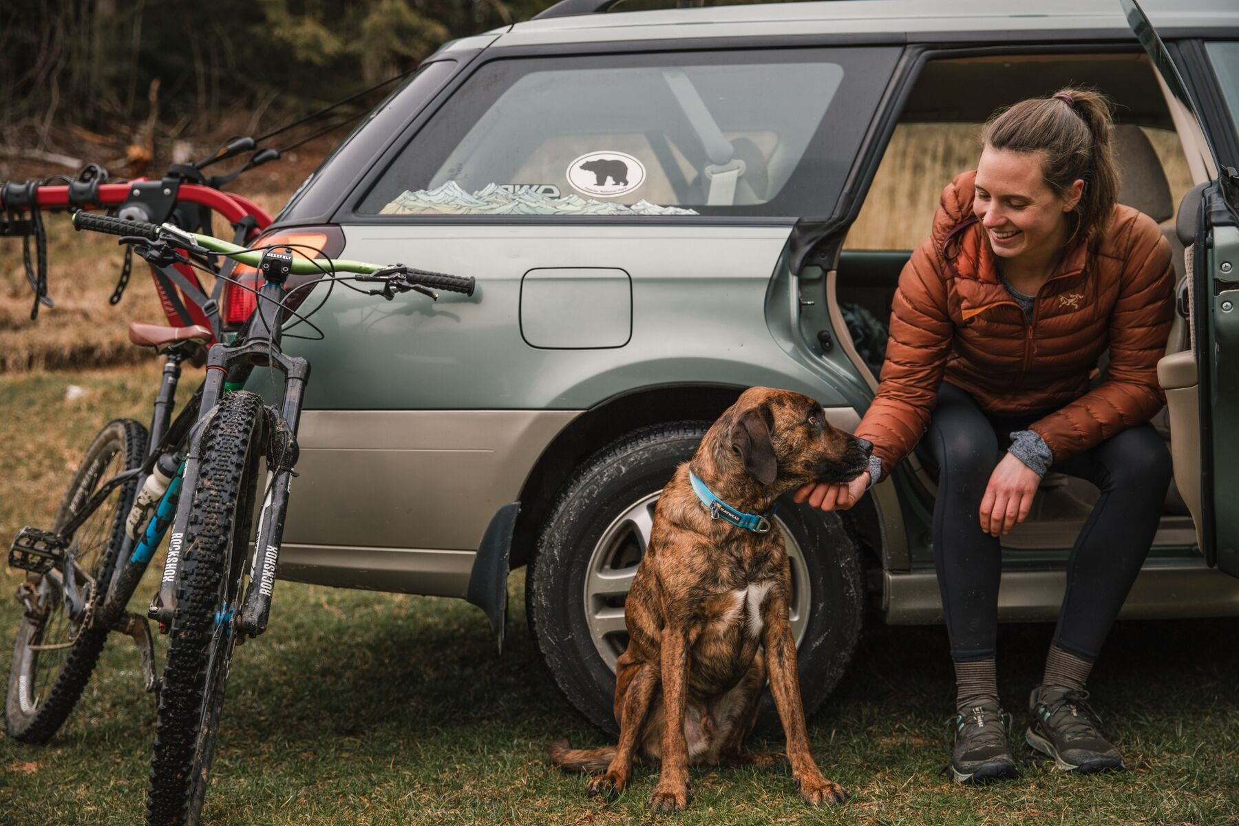 Woman petting dog at the car after mountain bike ride.