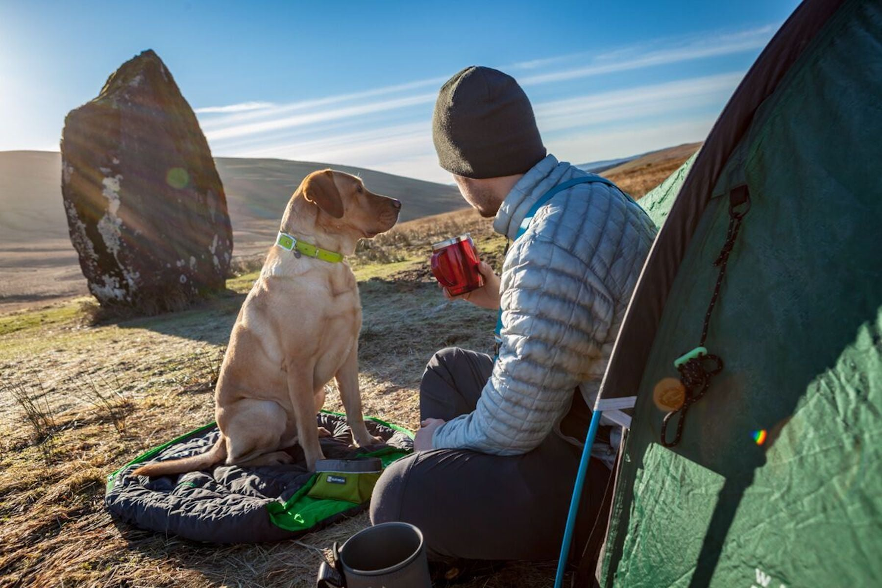 Dog and Human sitting outside their tent