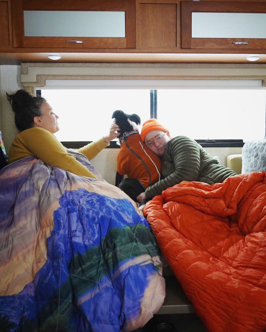 Two people with dog in Fernie sweater snuggled in sleeping bags by window.