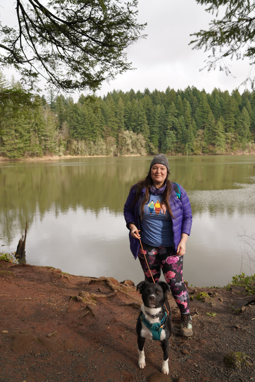 Jenny Bruso with dog in Flagline harness by the water on a hike.