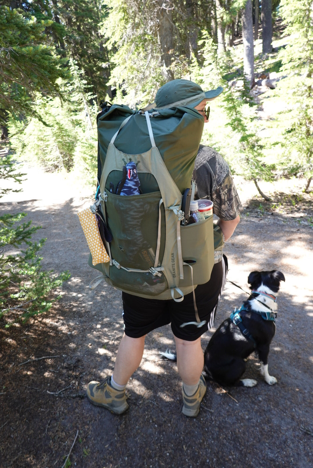 Woman with large backpacking pack stuffed full, with dog in front range harness at her side.