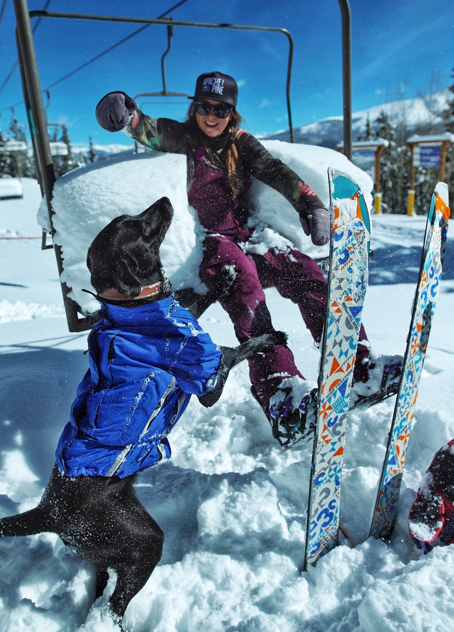 Leanne gets on a ski lift while her dog, Stout, looks up at her from the snow.