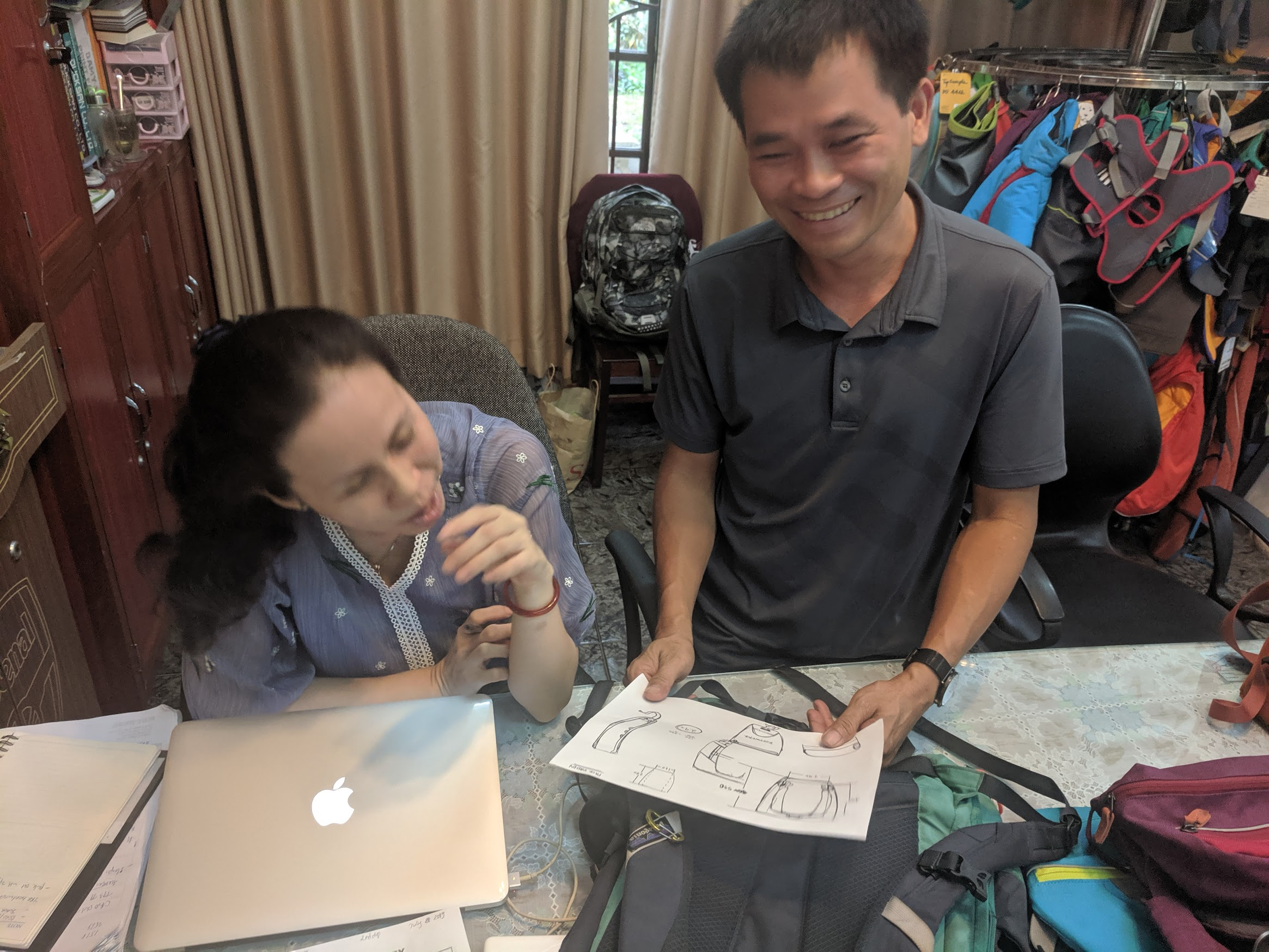 Vietnam team members holding sketches of the pack out bag.