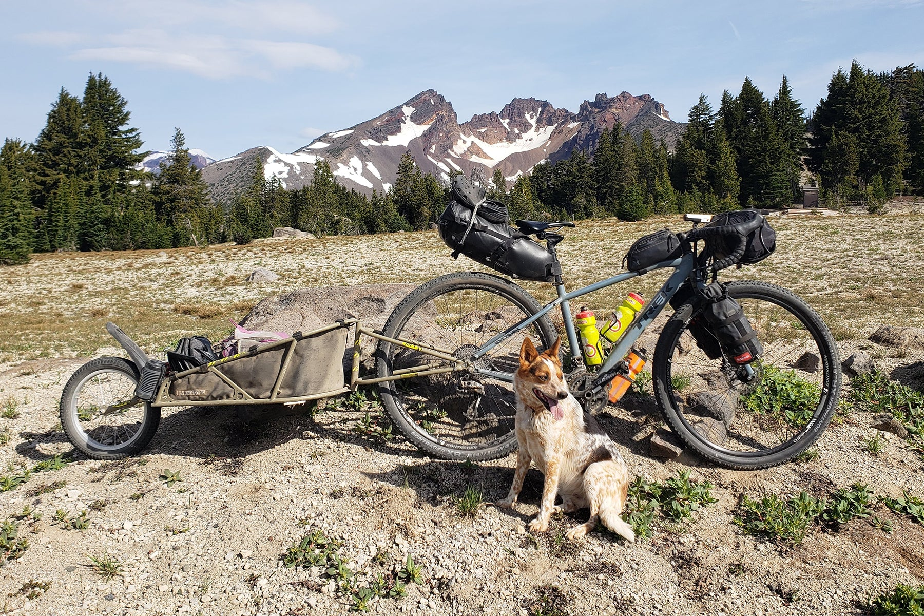 Emma next to the loaded up gravel bike setup with broken Top mountain in the background.